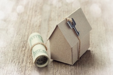46500589 - model of cardboard house with key and dollar bills. house building, loan, real estate, cost of housing or buying a new home concept.